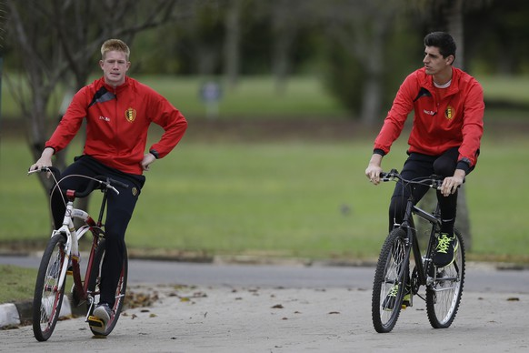 Belgium's Kevin De Bruyne, left, and goalkeeper Thibaut Courtois ride bicycles as they arrive at a training session of Belgium in Mogi Das Cruzes, Brazil, Thursday, June 19, 2014. Belgium play in group H of the 2014 soccer World Cup. (AP Photo/Andrew Medichini)