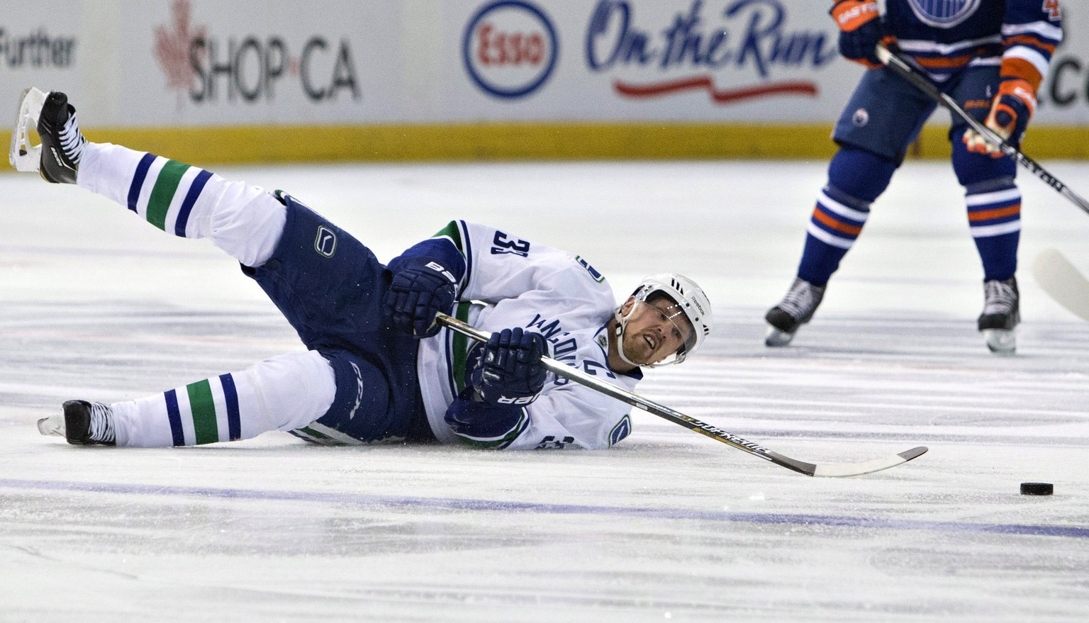 Vancouver Canucks' Henrik Sedin (33) falls as he goes for the puck against the Edmonton Oilers during the first period of an NHL hockey game Wednesday, Nov. 19, 2014, in Edmonton, Alberta. (AP Photo/The Canadian Press, Jason Franson)