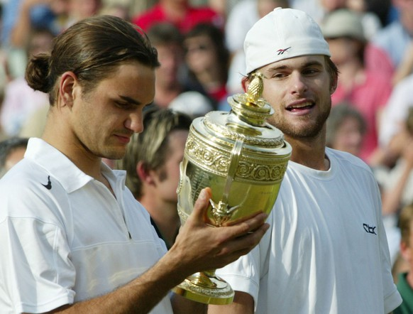 Roger Federer, left,   looks at winners the trophy as Andy Roddick looks across after  the  Men's Singles final on the Centre Court at Wimbledon, Sunday July 4, 2004. Federer won the match 4-6, 7-5, 7-6 (3), 6-4, to retain the title.  (AP Photo/Dave Caulkin)  **  EDITORIAL USE ONLY  **