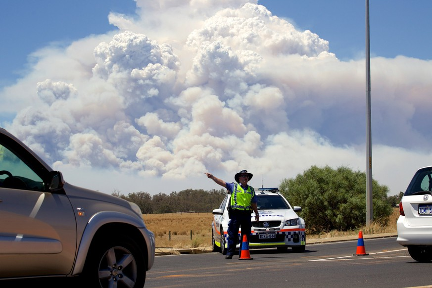 Smoke clouds from a large bush fire are seen behind a police road block at the turn off onto the South Western Highway near Pinjarra, Western Australia, January 7, 2016.    REUTERS/Richard Wainwright/AAP  ATTENTION EDITORS - THIS PICTURE WAS PROVIDED BY A THIRD PARTY. IT IS DISTRIBUTED EXACTLY AS RECEIVED BY REUTERS, AS A SERVICE TO CLIENTS. EDITORIAL USE ONLY. NOT FOR SALE FOR MARKETING OR ADVERTISING CAMPAIGNS. NO RESALES. NO ARCHIVE. AUSTRALIA OUT. NO COMMERCIAL OR EDITORIAL SALES IN AUSTRALIA. NEW ZEALAND OUT. NO COMMERCIAL OR EDITORIAL SALES IN NEW ZEALAND.      TPX IMAGES OF THE DAY