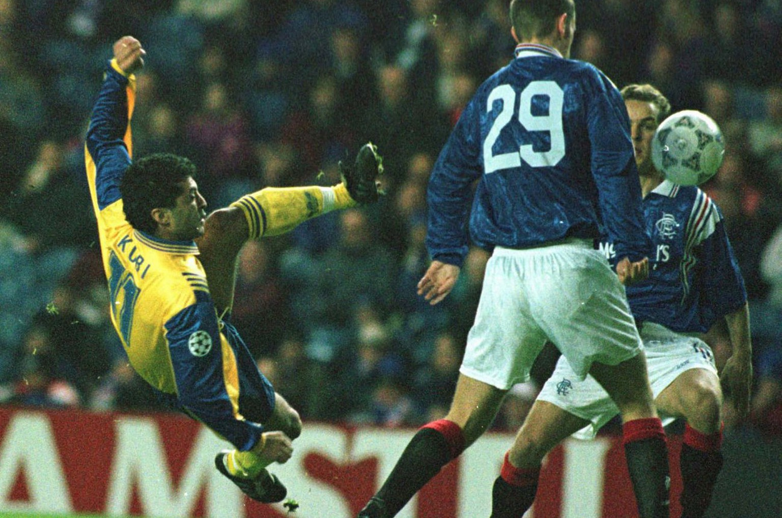 Kubilay Tuerkyilmaz (left) from Grasshoppers Zuerich fires a shot at the goal whilst Glasgow Rangers player Scott Wilson (29) looks on during the UEFA Champions League game between Glasgow Rangers and GC played at Ibrox stadium in Glasgow, Scotland, on Wednesday, November 20, 1996. (KEYSTONE/AP Photo/Dave Caulkin)