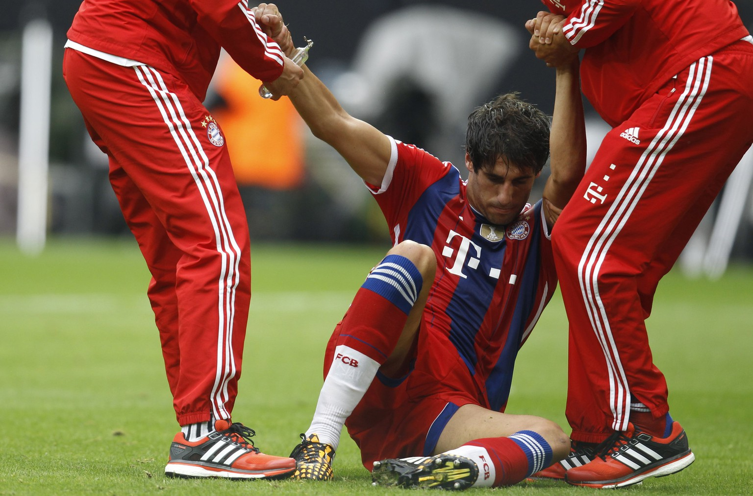Bayern Munich's Javier Martinez is assisted up after sustaining an injury to leave the field during the SuperCup 2014 soccer match against Borussia Dortmund in Dortmund August 13, 2014. REUTERS/Ina Fassbender (GERMANY - Tags: SPORT SOCCER) DFL RULES TO LIMIT THE ONLINE USAGE DURING MATCH TIME TO 15 PICTURES PER GAME. IMAGE SEQUENCES TO SIMULATE VIDEO IS NOT ALLOWED AT ANY TIME. FOR FURTHER QUERIES PLEASE CONTACT DFL DIRECTLY AT + 49 69 650050