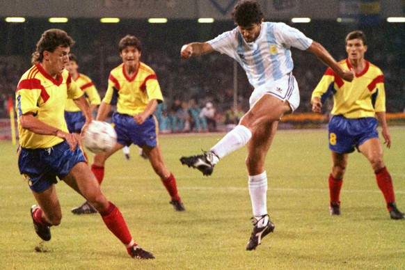 Argentina's Jorge Burruchaga shoots the ball past Romania's Gheorghe Popescu during the first minutes of the Soccer World Cup match between Argentina and Romania, in Naples, Italy, June 18, 1990. The game ended in a one all draw. (AP Photo/Foggia)
