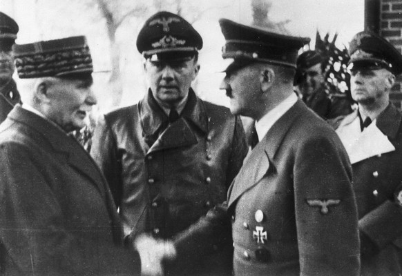FILE - This  Oct. 24, 1940 file photo shows German Chancellor Adolf Hitler, right, shaking hands with Head of State of Vichy France Marshall Philippe Petain, in occupied France. Behind centre is Paul Schmidt an interpreter and right is German Minister of Foreign Affairs Joachim Von Ribbentrop. France is opening police and legal archives from the collaborationist Vichy regime, allowing free access to previously classified documents from World War II. The order, signed Dec. 24 and effective Monday, allows anyone access to the archives that, among other things, show the extra-legal prosecution of members of the French Resistance, as well as proceedings against French Jews. (AP Photo, File)