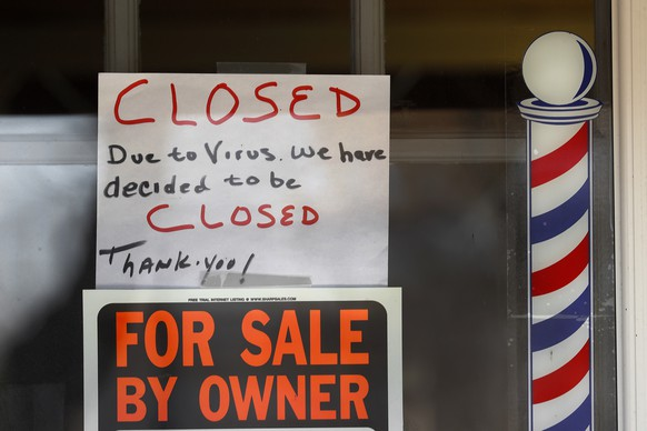 """""""For Sale By Owner"""" and """"Closed Due to Virus"""" signs are displayed in the window of Images On Mack in Grosse Pointe Woods, Mich., Thursday, April 2, 2020. The coronavirus outbreak has triggered a stunning collapse in the U.S. workforce with 10 million people losing their jobs in the past two weeks and economists warn unemployment could reach levels not seen since the Depression, as the economic damage from the crisis piles up around the world. (AP Photo/Paul Sancya)"""