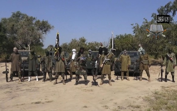 This image taken from video released late Friday evening, Oct. 31, 2014, by Boko Haram, Abubakar Shekau, centre, the leader of Nigeria's Islamic extremist group denies agreeing to any cease-fire with the government and says more than 200 kidnapped schoolgirls all have converted to Islam and been married off. In the new video released late Friday night, Abubakar Shekau dashed hopes for a prisoner exchange to get the girls released.