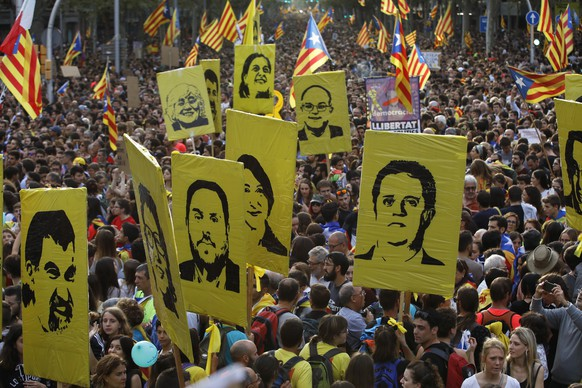Protestors hold pictures of Catalan high-profile separatist politicians, some jailed and others who are fugitives from Spanish law after fleeing the country, during a demonstration in Barcelona, Spain, Friday, Oct. 18, 2019.The Catalan regional capital is bracing for a fifth day of protests over the conviction of a dozen Catalan independence leaders. Five marches of tens of thousands from inland towns are converging in Barcelona's center for a mass protest. (AP Photo/Emilio Morenatti)