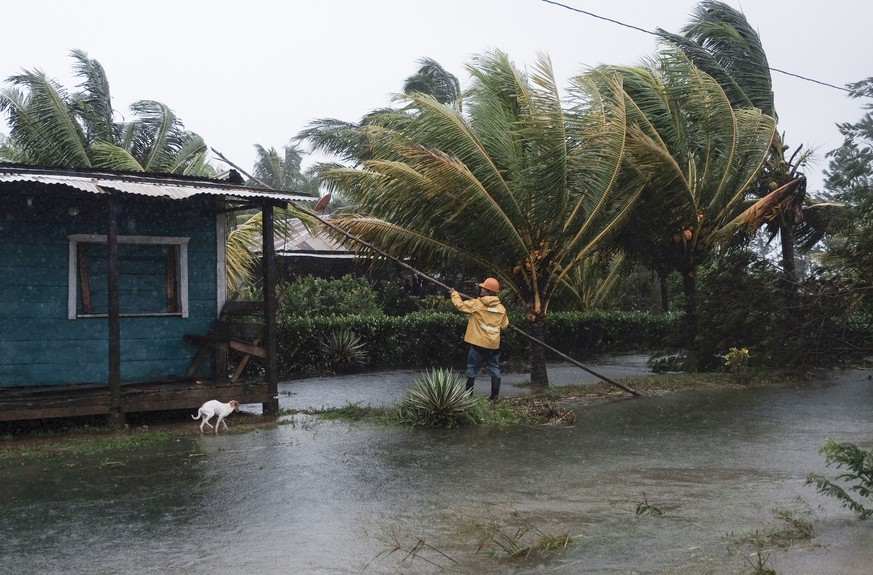 A man fixes the roof of a home surrounded by floodwaters brought on by Hurricane Eta in Wawa, Nicaragua, Tuesday, Nov. 3, 2020. Eta slammed into Nicaragua's Caribbean coast with potentially devastating winds Tuesday, while heavy rains thrown off by the Category 4 storm already were causing rivers to overflow across Central America. (AP Photo/Carlos Herrera)