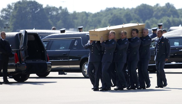 A coffin of one of the victims of Malaysia Airlines MH17 downed over rebel-held territory in eastern Ukraine, is loaded into a hearse on the tarmac during a national reception ceremony at Eindhoven airport July 23, 2014. Two aircraft carrying the remains of some of the 298 passengers who died on flight MH17 touched down at an airport in the Dutch city of Eindhoven on Wednesday, as next-of-kin and Dutch and foreign officials looked on. The remains of the victims of the downing of the flight over eastern Ukraine, 193 of whom were Dutch, will be brought over the next few days to a military base in Hilversum, the Netherlands. The Netherlands declared Wednesday the country's first day of mourning in more than half a century.      REUTERS/Francois Lenoir (NETHERLANDS  - Tags: TRANSPORT POLITICS DISASTER CIVIL UNREST)