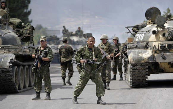 FILE- In this file photo taken on Thursday, Aug. 14, 2008, Russian soldiers block the road on the outskirts of Gori, northwest of the capital Tbilisi, Georgia.  Russia's Prime Minister Dmitry Medvedev in an interview broadcast by Russian state television Tuesday Aug. 7, 2018, on the 10th anniversary of the Russia-Georgia war, issued a stern warning that incorporating Georgia into NATO could trigger a new