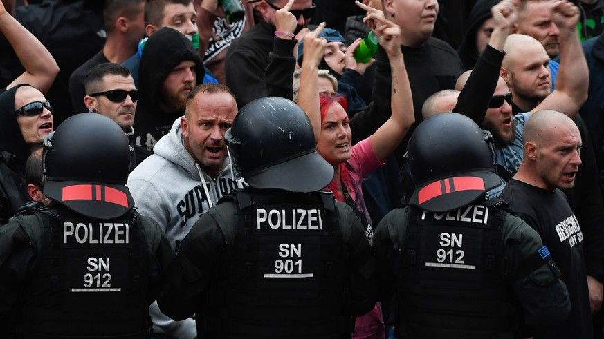 epa06977356 Right wing protesters gesture towards police in riot gear as they gather at the place where a man was stabbed in the night of the 25 August 2018, in Chemnitz, Germany, 27 August 2018. A 35-year-old man reportedly was stabbed and died shortly after what police described as a 'scuffle between members of different nationalities' at a city festival. The incident kept police and the city government busy since then as there were several spontaneous marches of hundreds of right-wing supporters in Chemnitz.  EPA/FILIP SINGER