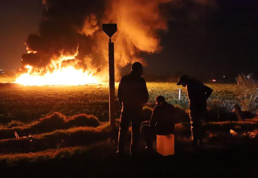 epaselect epa07298870 People wait in front of a wall of fire after an explosion of an illegal tap on Mexican oil company Pemex's pipeline in Tlahuilipan, state of Hidalgo, Mexico, late night 18 January 2019. At least 21 people died and 71 other people were wounded in the blast, according to official sources.  EPA/OASA