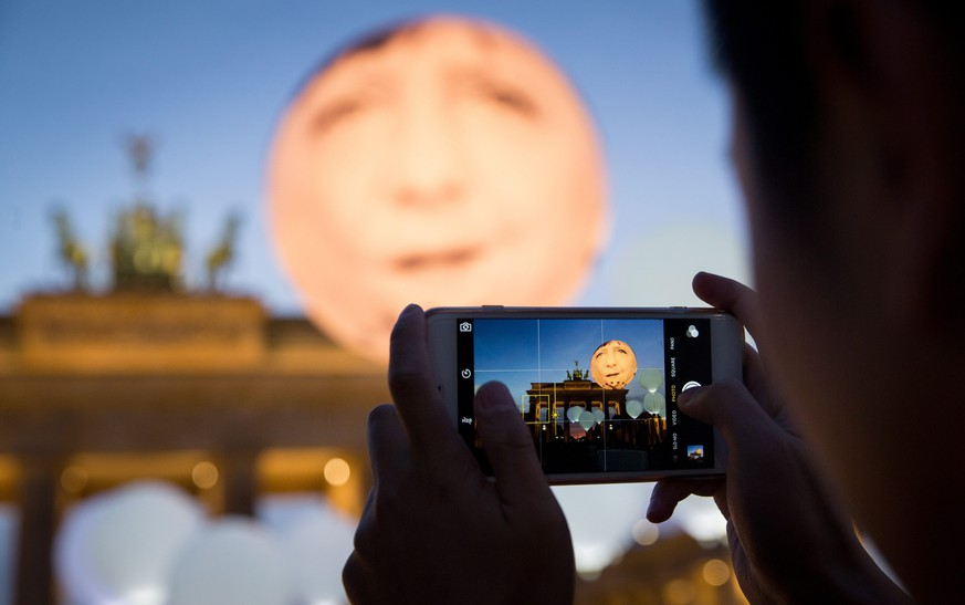 epa04947378 A tourist takes a picture of a giant balloon featuring the face of German chancellor Angela Merkel as it floats amid smaller white balloons in front of the Brandenburg Gate, a major landmark of Berlin, Germany, 24 September 2015. The advocacy organisation 'ONE Campaign' is hosting the event to draw attention to the global aims of the United Nations (UN) including sustainable development and the struggle against extreme poverty ahead of the chancellor's visit to New York, USA.  EPA/KAY NIETFELD