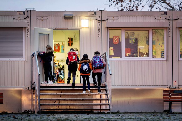 Pupils go to a school which is partially located in containers in Frankfurt, Germany, Monday, Dec. 14, 2020. Germany goes into a lockdown on Wednesday, Dec. 16, 2020. (AP Photo/Michael Probst)