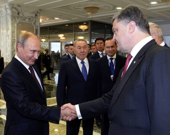 epa04381668 (FILE) A file photo dated 26 August 2014 of Russian President Vladimir Putin (2-L) shaking hands with Ukrainian President Petro Poroshenko (R) as Kazakh President Nursultan Nazarbayev (C) looks at them prior their talks in Minsk, Belarus. Media reports on 03 September 2014 state that the presidents of Ukraine and Russia, Petro Poroshenko and Vladimir Putin, agreed on a permanent ceasefire, according to Poroshenko's office. The agreement was reportedly reached during a telephone conversation.  EPA/SERGEI BONDARENKO / POOL