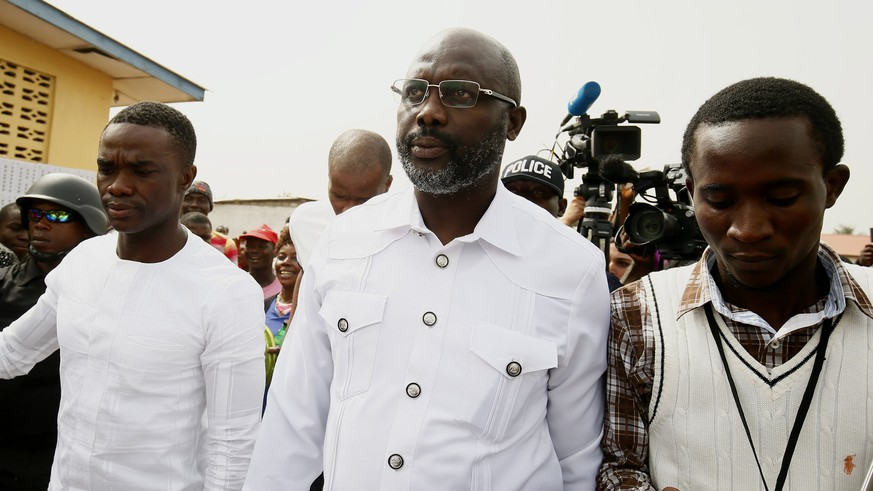 epa06405957 Liberian presidential candidate for the Coalition for Democratic Change (CDC), George Weah (C) leaves a polling station after casting his ballot in presidential elections run-off in Monrovia, Liberia, 26 December 2017. Some 2.1 million registered Liberian voters are eligible to vote in the presidential run-off between George Weah, of the Coalition for Democratic Change (CDC), and Joseph Nyuma Boakai of the governing Unity Party (UP).  EPA/AHMED JALLANZO