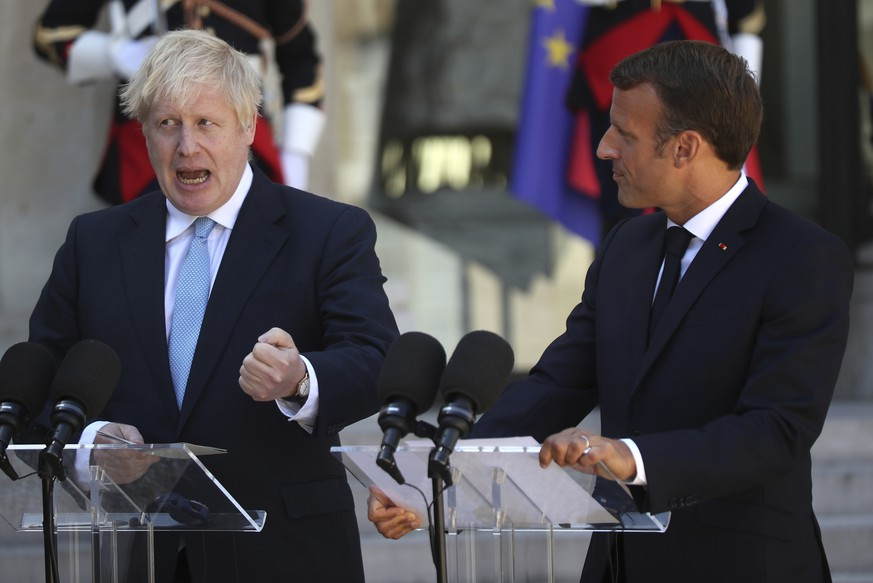 French President Emmanuel Macron and Britain's Prime Minister Boris Johnson speak to the media outside the Elysee Palace, Thursday, Aug. 22, 2019 in Paris. Welcoming British Prime Minister Boris Johnson to the courtyard of his Elysee Palace Thursday with a big smile and little pats on the back, Macron remained firm on his position that renegotiating the deal for Britain to leave the European Union is not an option. (AP Photo/Daniel Cole)