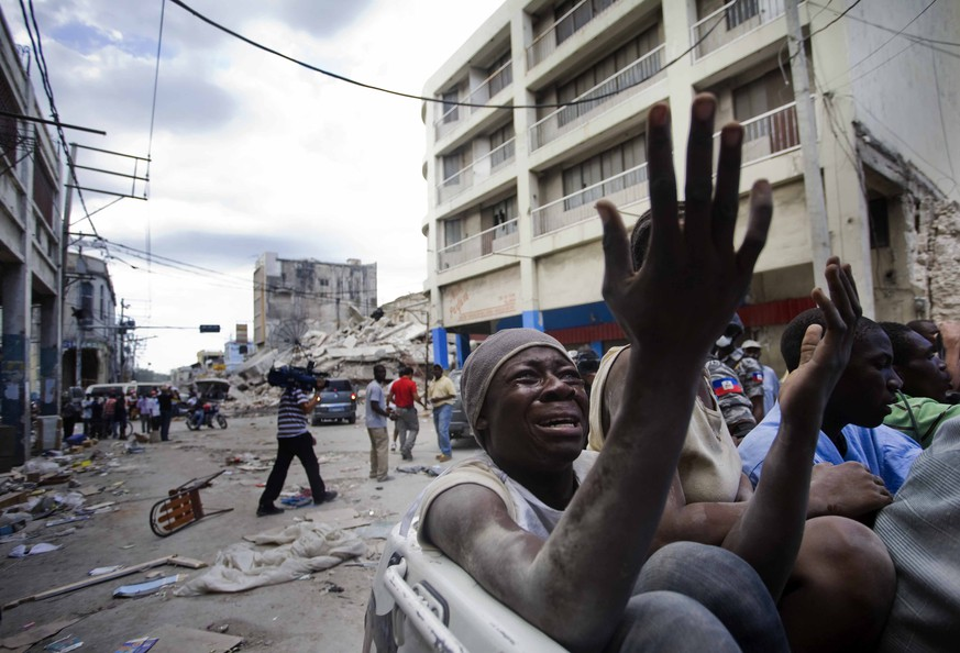 ZUM 5. JAHRESTAG DES ERDBEBENS IN HAITI AM MONTAG, 12. JANUAR 2015, STELLEN WIR IHNEN FOLGENDES BILDMATERIAL ZUR VERFUEGUNG - In this photo taken Saturday, Jan. 16, 2010, released by China's Xinhua News Agency, a man cries as he rides on a truck traveling past  collapsed buildings following Tuesday's devastating earthquake, in Port-au-Prince, the capital of Haiti. Prayers of thanksgiving and cries for help rose from Haiti's huddled homeless Sunday, the sixth day of an epic humanitarian crisis that was straining the world's ability to respond and igniting flare-ups of violence amid the rubble of Port-au-Prince. (KEYSTONE/AP Photo/Xinhua, David de la Paz)