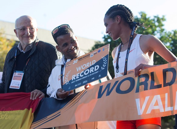 epa09542780 Ethiopian athlete Letesenbet Gidey (R), accompanied by her coach and by the president of Trinidad Foundation, Juan Roig (L) reacts after breaking the world record at Valencia Half Marathon in the coastal city of Valencia, eastern Spain, 24 October 2021. Gidey has set an official time of 1:02:52, lowering by 1 minute and 10 seconds the previous world record set by Kenyan Ruth Chepngetich last April.  EPA/Miguel Angel Polo