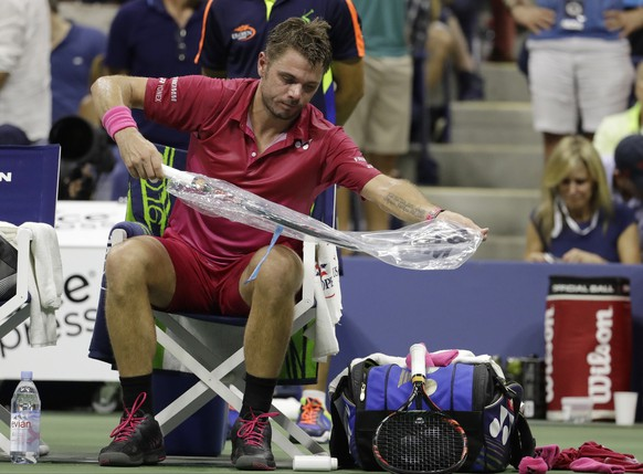 Stan Wawrinka, of Switzerland, changes out his racket during a break between games against Kei Nishikori, of Japan, during the semifinals of the U.S. Open tennis tournament, Friday, Sept. 9, 2016, in New York. (AP Photo/Julio Cortez)