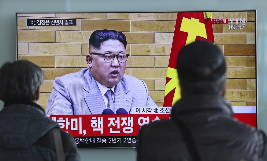 South Koreans watch a TV news program showing North Korean leader Kim Jong Un's New Year's address, at the Seoul Railway Station in Seoul, South Korea, Monday, Jan. 1, 2018. The part of letters on the bottom