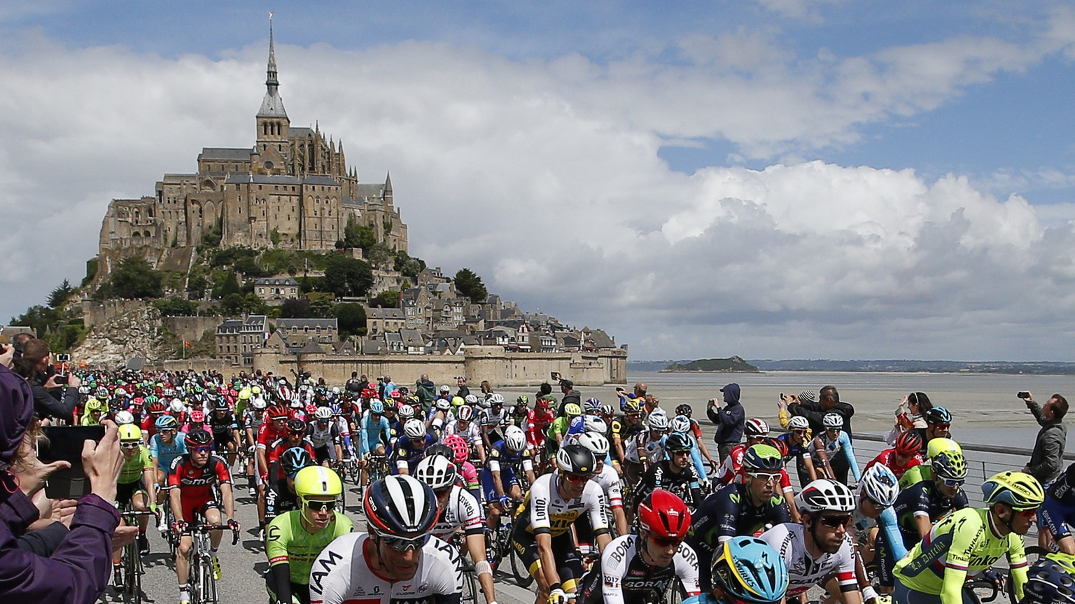 The pack takes the start at the Mont-Saint-Michel, rear, during the first stage of the Tour de France cycling race over 188 kilometers (116.8 miles) with start in Mont-Saint-Michel and finish in Utah Beach, France, Saturday, July 2, 2016. (AP Photo/Christophe Ena)