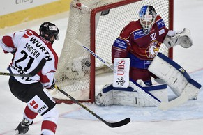 epa04543078 Geneva's goalkeeper Janick Schwendener, (R), fights for the puck against Team Canada's Jerome Samson during the game between Switzerland's Geneve Servette HC and Team Canada in the semi final game at the 88th Spengler Cup ice hockey tournament in Davos, Switzerland, 30 December 2014.  EPA/PETER SCHNEIDER