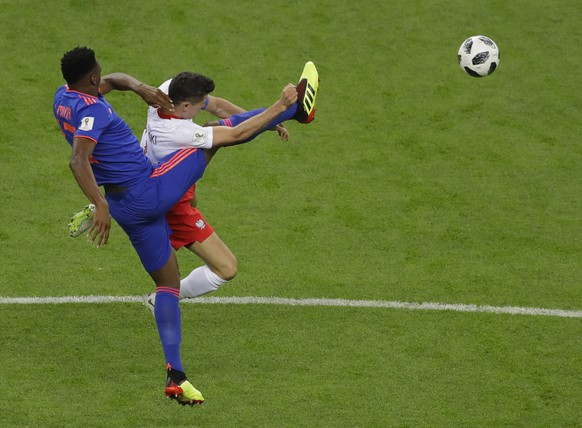 Colombia's Yerry Mina, left, and Poland's Robert Lewandowski collide during the group H match between Poland and Colombia at the 2018 soccer World Cup at the Kazan Arena in Kazan, Russia, Sunday, June 24, 2018. (AP Photo/Sergei Grits)