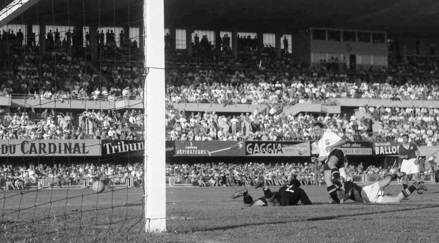 Austria's Theodor Wagner, in white shirt, shoots past Swiss goalkeeper Eugene Parlier to score Austria's sixth goal in the World Cup quarter-final match between Switzerland and Austria, in Lausanne, June 26, 1954. Austria won the match 7-5. (AP Photo)
