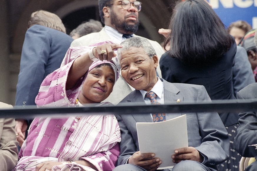 FILE - This June 20, 1990 file photo shows Winnie Mandela pointing out something in the crowd to her husband Nelson Mandela, during a welcoming ceremony at New York's City Hall as they kicked of a three-day stay in the city. The FBI investigated multiple death threats against Nelson Mandela during his 1990 visit to the United States and relied on an informant for details about the anti-apartheid leader's trip, according to newly released documents. The FBI released hundreds of pages of records tied to Mandela's visit, which came months after was released from a 27-year prison sentence in South Africa and four years before he became president. (AP Photo/David Longstreath, File)