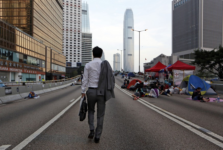 A man walks to work as the pro-democracy student protesters sleep on a roadside in the occupied areas surrounding the government complex in Hong Kong Oct. 6, 2014. Hong Kong's civil servants returned to work and schools were reopening Monday as a massive pro-democracy protest that has occupied much of the city center for the week dwindled. (AP Photo/Kin Cheung)