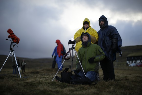 Italian visitors wait for the start of a total solar eclipse on a hill beside a hotel overlooking the sea and Torshavn, the capital city of the Faeroe Islands, Friday, March 20, 2015. For months, even years, accommodation on the remote Faeroe Islands has been booked out by fans who don't want to miss an almost three-minute-long astronomical sensation. Now they just have to hope the clouds will blow away so they can fully experience Friday's brief total solar eclipse.  (AP Photo/Matt Dunham)
