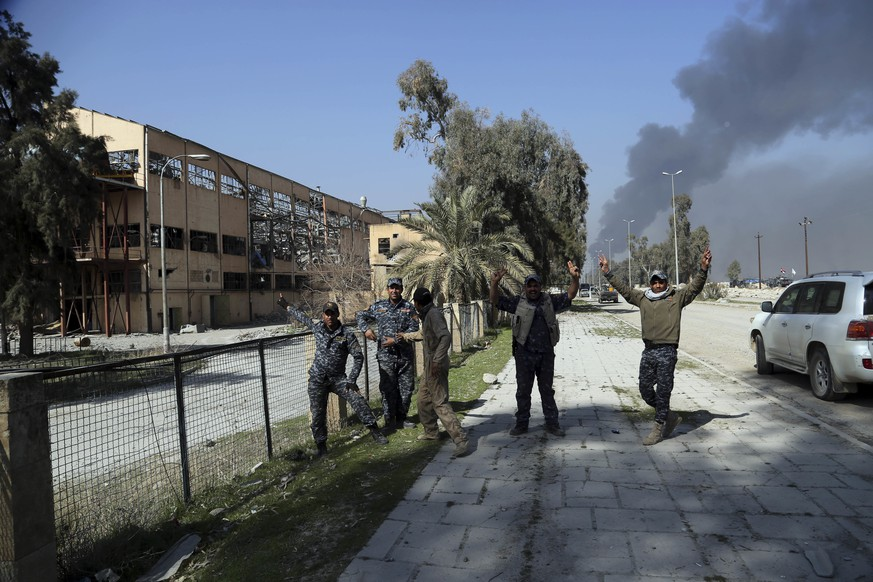 Iraqi Federal policemen celebrate their victory while standing between the liberated airport and sugar plant in western Mosul, Iraq, Feb. 24. 2017. Iraqi forces pushed into the first neighborhood in western Mosul on Friday and took full control of the international airport on the city's southwestern edge from the Islamic State group, according to Iraqi officials. (AP Photo/ Khalid Mohammed)