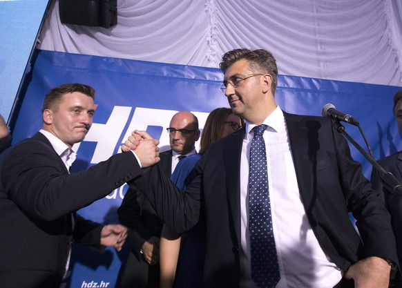 epa05535682 Leader of the Croatian Democratic Union (HDZ) Andrej Plenkovic (R) celebrates the victory of his party in the parliamentary elections in downtown Zagreb, Croatia, 11 September 2016. According to first projections, the HDZ won 62 seats in Croatia's 151-seat parliament, defeating the 52 eats of Prime Minister Milanovic's Social Democratic Party (SDP).  EPA/ANTONIO BAT