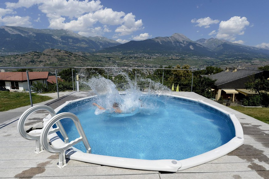 Line and Etienne enjoy their pool, Saturday, July 27, 2013, above Sion, Switzerland. (KEYSTONE/Maxime Schmid)