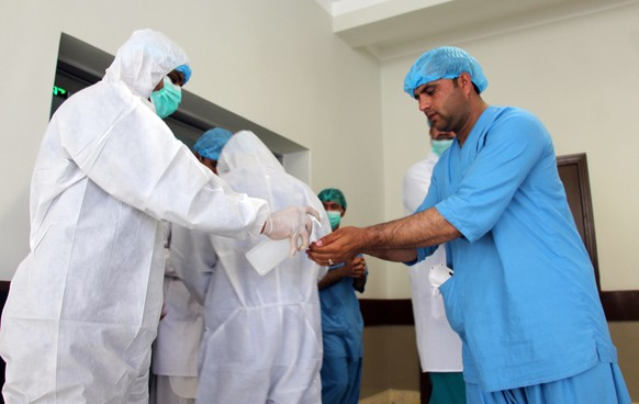 epa08296993 Hospital staff wear hazmet suits inside the coronavirus center in Kandahar, Afghanistan, 16 March 202?0. Reports state th?e number of cases infected with coronavirus in Afghanistan increased to 16.  EPA/M SADIQ