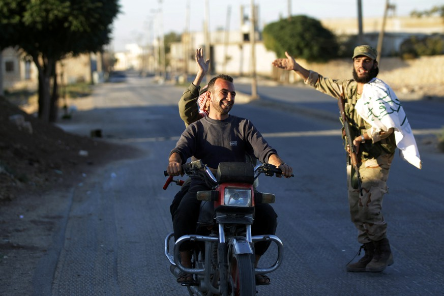 REFILE - CORRECTING STYLE OF TOWN NAMEResidents driving a motorcycle gesture towards a fighter in Dabiq town, northern Aleppo countryside, Syria October 16, 2016. REUTERS/Khalil Ashawi
