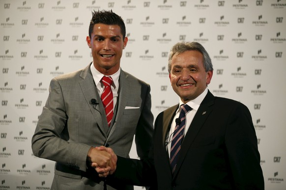 Portuguese player Cristiano Ronaldo shakes hands with Dionisio Pestana, President of the Pestana Group, during a publishing event in Lisbon, Portugal December 17, 2015. The Pestana Group, the largest hotel group in Portugal, established a partnership with soccer player Cristiano Ronaldo for a joint investment of 75 million euros in four new hotels in Lisbon, Funchal, New York and Madrid.  REUTERS/Rafael Marchante