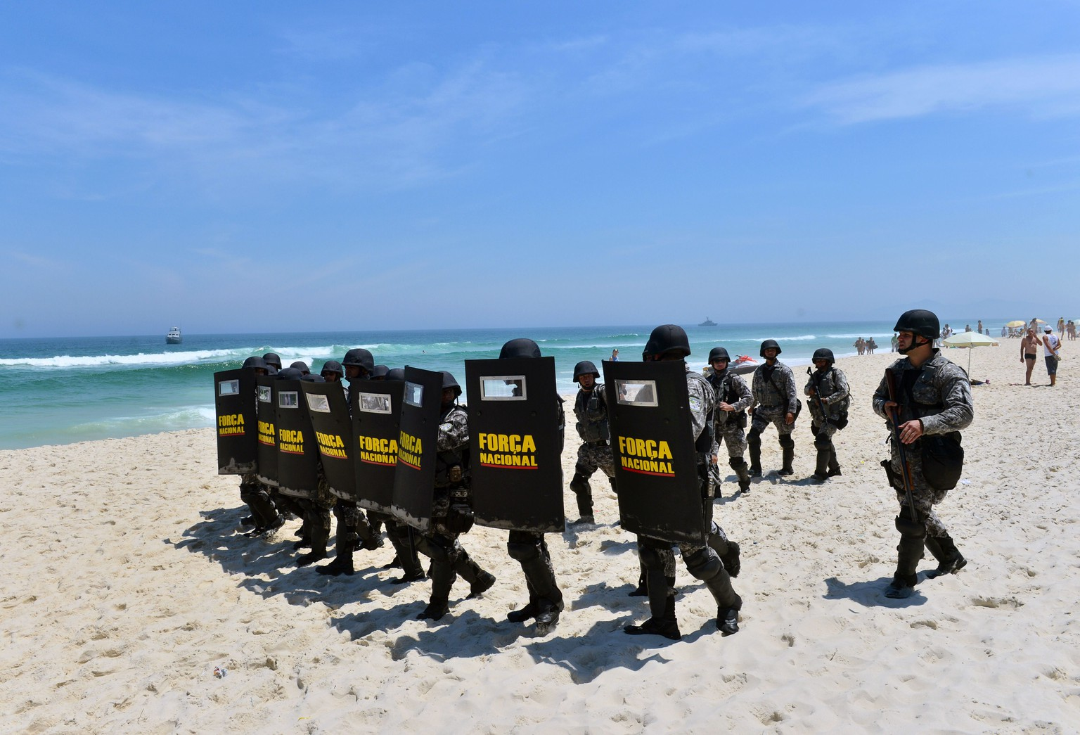 Brazil's Forca Nacional security personnel in riot gear charge on demonstrators at the beach in front of the hotel where Brazil's National Petroleum Agency (ANP) will auction drilling rights to one of the world's largest offshore oil discoveries, in Barra de Tijuca, Rio de Janeiro, Brazil on October 21, 2013. The security plan for the upcoming FIFA World Cup covers from a terrorist attack to a fight between football fans, though street protests continue to be the main worry for authorities.AFP PHOTO/CHRISTOPHE SIMON