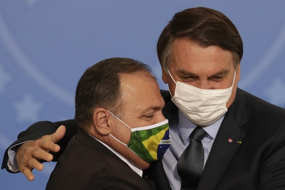 FILE - In this Sept. 16, 2020 file photo, wearing masks to curb the spread of COVID-19, Brazil's President Jair Bolsonaro, right, greets Health Minister Gen. Eduardo Pazuelo, left, during a ceremony at the Planalto Presidential Palace, in Brasilia, Brazil. President Bolsonaro confirmed Monday, March 15, 2021, that he will replace Pazuello as COVID-19 deaths and hospitalizations rise dramatically. (AP Photo/Eraldo Peres, File) Jair Bolsonaro,Eduardo Pazuelo