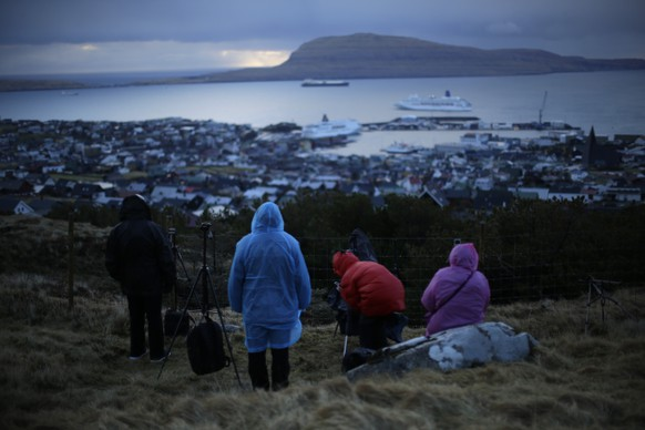 People wait for the start of a total solar eclipse on a hill beside a hotel overlooking the sea and Torshavn, the capital city of the Faeroe Islands, Friday, March 20, 2015. For months, even years, accommodation on the remote Faeroe Islands has been booked out by fans who don't want to miss an almost three-minute-long astronomical sensation. Now they just have to hope the clouds will blow away so they can fully experience Friday's brief total solar eclipse.  (AP Photo/Matt Dunham)