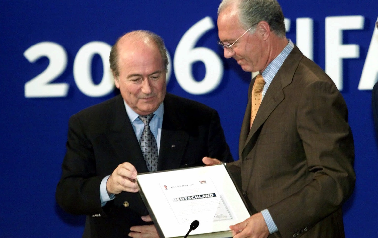 FILE - In this July 6, 2000 file picture FIFA president Joseph Blatter, left, hands over the World Cup documents to Franz Beckenbauer of the German delegation in Zurich, Switzerland,  after soccer's world governing body FIFA announced Germany will host the soccer World Cup 2006.  A highly anticipated independent report to be released Friday March 4, 2016 could throw light into corruption allegations against Germany's 2006 World Cup organizers and the fate of a dubious payment to FIFA.  (AP Photo/Diether Endlicher,file)