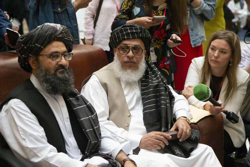 Mullah Abdul Ghani Baradar, the Taliban group's top political leader, left, and Sher Mohammad Abbas Stanikzai, the Taliban's chief negotiator speak to the media  Russia, Tuesday, May 28, 2019. Baradar, the Taliban group's top political leader, and a delegation of Taliban are in Moscow where they are meeting other Afghans including former President Hamid Karzai and some of the candidates in the presidential elections. (AP Photo/Alexander Zemlianichenko)