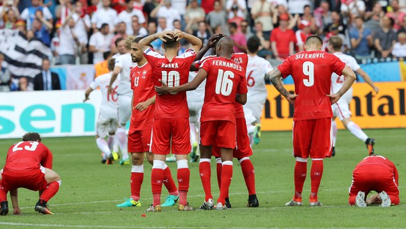Swiss players react after Poland's Grzegorz Krychowiak scored the decisive penalty, during the Euro 2016 round of 16 soccer match between Switzerland and Poland, at the Geoffroy Guichard stadium in Saint-Etienne, France, Saturday, June 25, 2016. Poland won 5-4 in a shootout. (AP Photo/Laurent Cipriani)