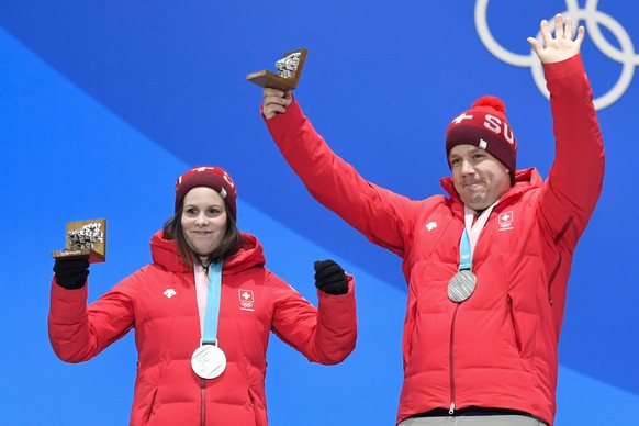 Jenny Perret and Martin Rios of Switzerland (silver medal), left, react next to Kaitlyn Lawes and John Morris of Canada (gold medal), from left, during the victory ceremony on the Medal Plaza for the mixed doubles final curling match at the XXIII Winter Olympics 2018 in Pyeongchang, South Korea, on Wednesday, February 14, 2018. (KEYSTONE/Gian Ehrenzeller)