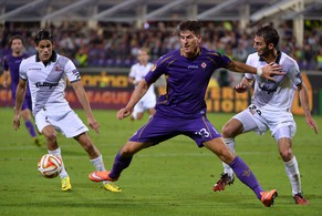 Fiorentina's German forward Mario Gomez (C) fights for the ball with Guingamp's French defender Dorian Leveque (L) and Guingamp's forward Mana Dembele during the Europa League group K  football match Fiorentina vs Guingamp on September 18, 2014 at the Artemio Franchi stadium in Florence. AFP PHOTO / ALBERTO PIZZOLI