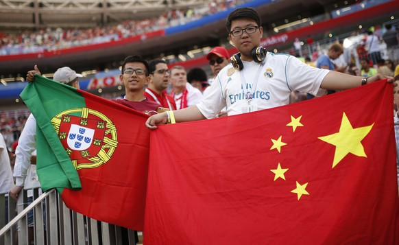 Fans display flags of China, right, and Portugal, left, prior the group B match between Portugal and Morocco at the 2018 soccer World Cup in the Luzhniki Stadium in Moscow, Russia, Wednesday, June 20, 2018. (AP Photo/Francisco Seco)