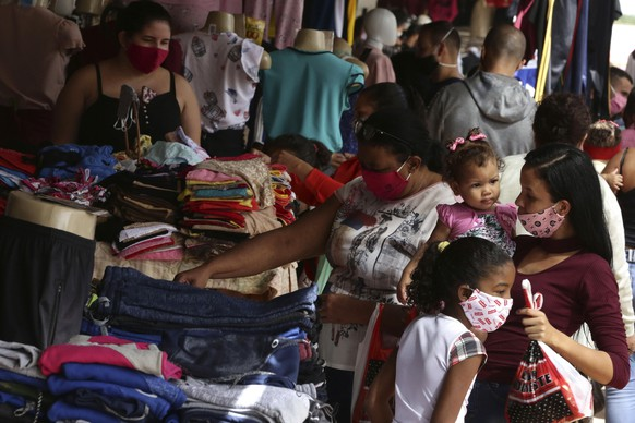 People wearing face masks shop at street side clothing stores in Brasilia, Brazil, Monday, May 18, 2020. Starting Monday, the city government authorized the opening of some commerce, such as apparel, amid the COVID-19 pandemic. (AP Photo/Eraldo Peres)