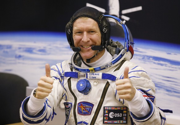 FILE - In this Tuesday, Dec. 15, 2015 file photo, British astronaut Tim Peake, member of the main crew of the expedition to the International Space Station (ISS), gestures prior the launch of Soyuz TMA-19M space ship at the Russian leased Baikonur cosmodrome, Kazakhstan. Anyone can dial a wrong number, but it's not often done from outer space. Peake tweeted an apology on Christmas Day from the International Space Station after calling a wrong number. (AP Photo/Dmitry Lovetsky, File)