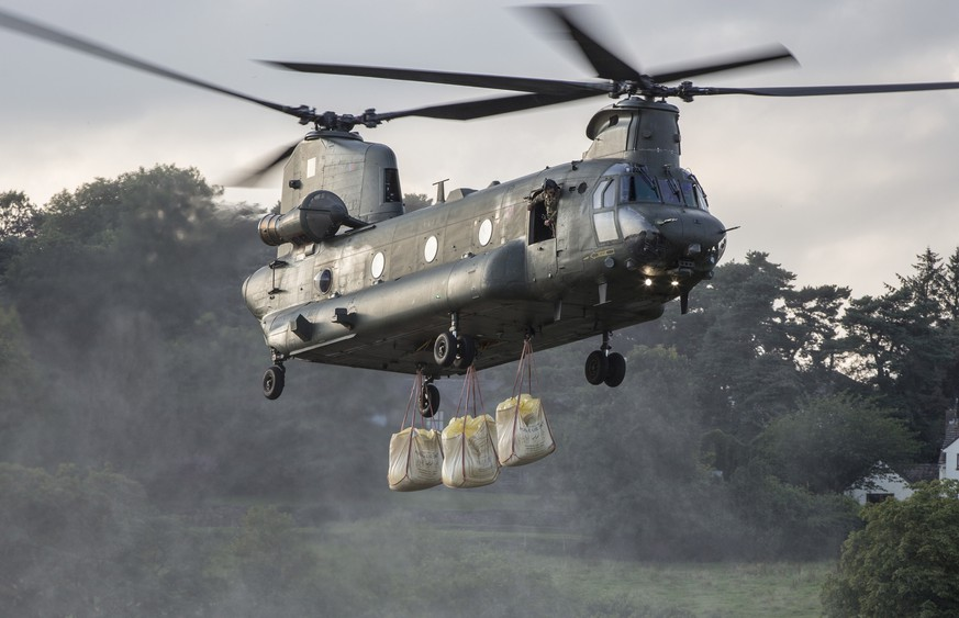 epa07754118 A handout picture provided by the British Ministry of Defence showing a British Royal Air Force Chinook Mk6a helicopter approaches with the load to drop on the dam in Whaley Bridge, Derbyshire, Britain, 02 August 2019, in the emergency operation to save the market town from severe flooding. The British Royal Air Force (RAF) Odiham Chinook Force has been called in to help spread sandbags over dam wall in Whaley Bridge. Around 400 tonnes of aggregate brought in to divert water and the town has been evacuated.  About 1,500 residents of Whaley Bridge, Derbyshire have been evacuated on 01 August over fears their town could be flooded after heavy rain damaged the dam holding back the Toddbrook reservoir.  EPA/Cpl Rob Travis RAF /BRITISH MINISTRY OF DEFENCE / HANDOUT MANDATORY CREDIT: MOD/CROWN COPYRIGHT HANDOUT EDITORIAL USE ONLY/NO SALES